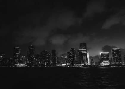 grey cloudy sky over the city by the harbor at nighttime